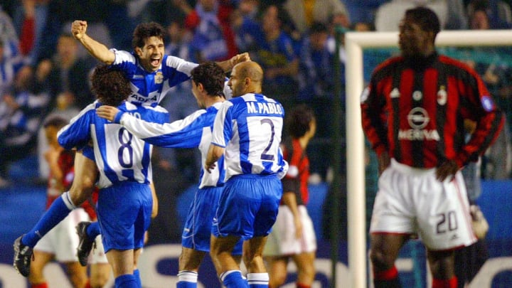 Deportivo La Coruna's players celebrate as Clarence Seedorf looks dejected