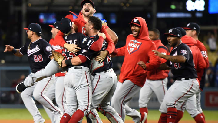LOS ANGELES, CALIFORNIA - OCTOBER 09: Daniel Hudson #44, Sean Doolittle #63 and catcher Yan Gomes #10 of the Washington Nationals celebrate the final out of the tenth inning as the Nationals defeated the Los Angeles Dodgers 7-3 in game five to win the National League Division Series at Dodger Stadium on October 09, 2019 in Los Angeles, California. (Photo by Harry How/Getty Images)