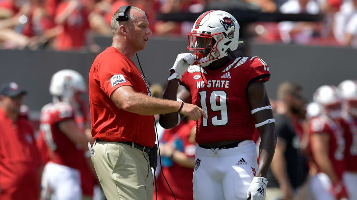 RALEIGH, NORTH CAROLINA - AUGUST 31: Head coach Dave Doeren talks with Cecil Powell #19 of the North Carolina State Wolfpack during their game against the East Carolina Pirates at Carter-Finley Stadium on August 31, 2019 in Raleigh, North Carolina. (Photo by Grant Halverson/Getty Images)