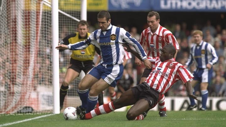Eric Cantona of Manchester United (left) scrambles for the ball with Ulrich Van Gobbel