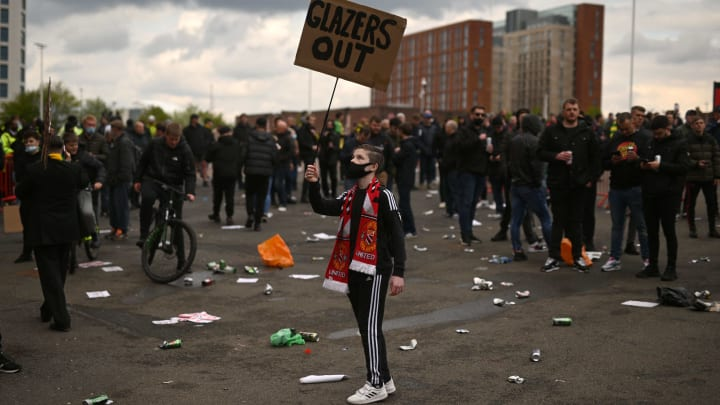 Amid the chaos, a young Man Utd fan holds a 'Glazers Out' sign aloft