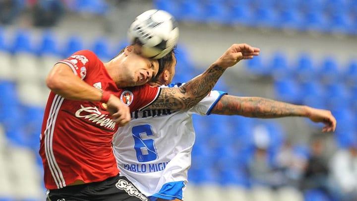 Jugadores de Puebla y Tijuana pelean por un balón.