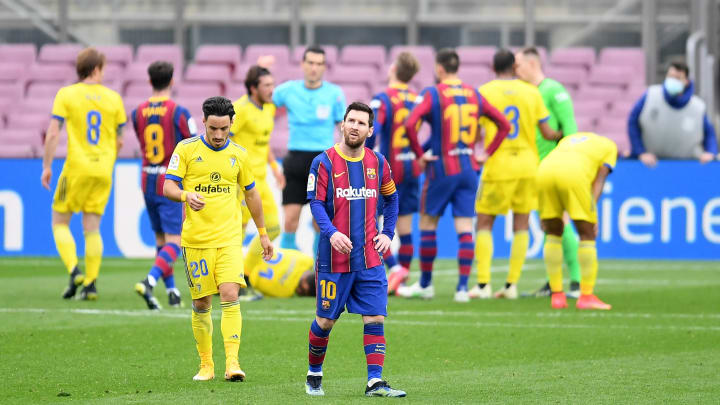 Lionel Messi looks dejected after he penalty award in the background
