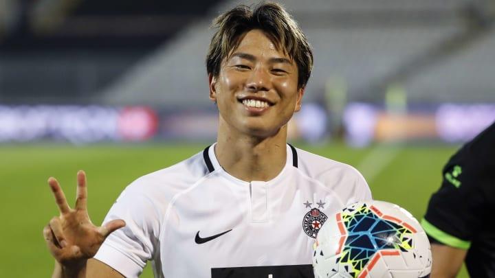 Takuma Asano posiert für die Kamera mit dem Partizan-Trikot