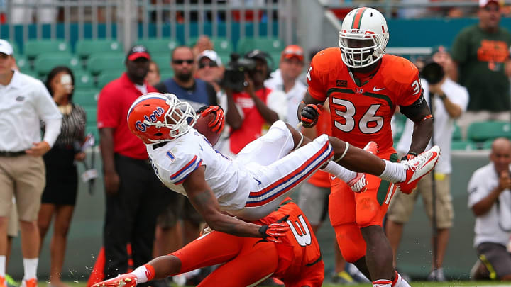MIAMI GARDENS, FL - SEPTEMBER 07: Quinton Dunbar #1 of the Florida Gators is tackled by Stacy Coley #3 of the Miami Hurricanes during a game  at Sun Life Stadium on September 7, 2013 in Miami Gardens, Florida.  (Photo by Mike Ehrmann/Getty Images)