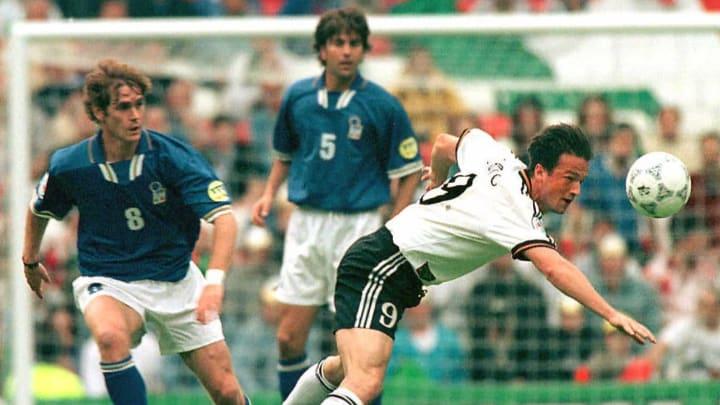 German Fredi Bobic (R) stretches for a header just