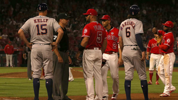 ANAHEIM, CALIFORNIA - JULY 16: Umpire Jim Reynolds #77 stands in front of Albert Pujols #5 of the Los Angeles Angels after Pujols talked at the Houston Astros dugout during the sixth inning of the MLB game between the Houston Astros and the Los Angeles Angels at Angel Stadium of Anaheim on July 16, 2019 in Anaheim, California. (Photo by Victor Decolongon/Getty Images)