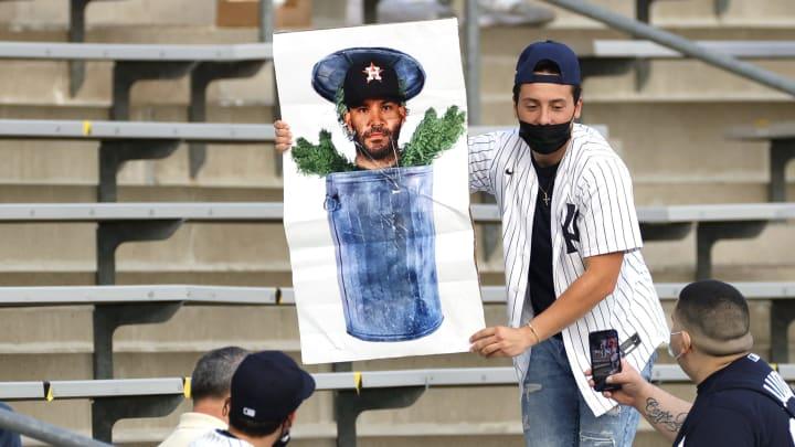 A Yankees fan holds an anti-Jose Altuve sign.