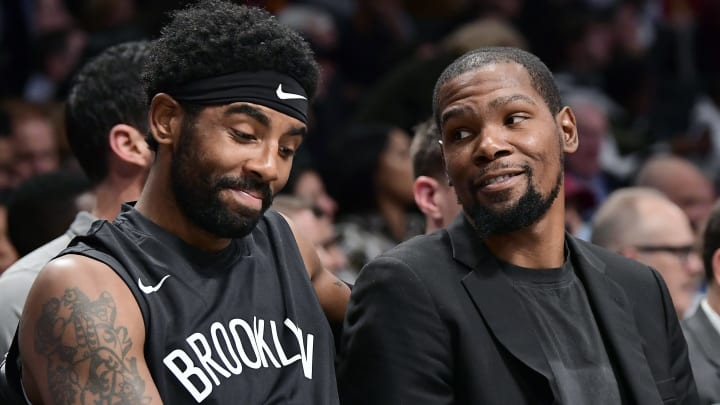 NEW YORK, NEW YORK - NOVEMBER 01:  Kyrie Irving #11 and Kevin Durant #7 of the Brooklyn Nets speak on the bench against the Houston Rockets at Barclays Center on November 01, 2019 in New York City. NOTE TO USER: User expressly acknowledges and agrees that, by downloading and/or using this photograph, user is consenting to the terms and conditions of the Getty Images License Agreement. (Photo by Steven Ryan/Getty Images)