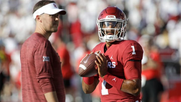 NORMAN, OK - SEPTEMBER 01:  Quarterback Jalen Hurts #1 warms up while head coach Lincoln Riley of the Oklahoma Sooners watches before the game against the Houston Cougars at Gaylord Family Oklahoma Memorial Stadium on September 1, 2019 in Norman, Oklahoma. The Sooners defeated the Cougars 49-31. (Photo by Brett Deering/Getty Images)