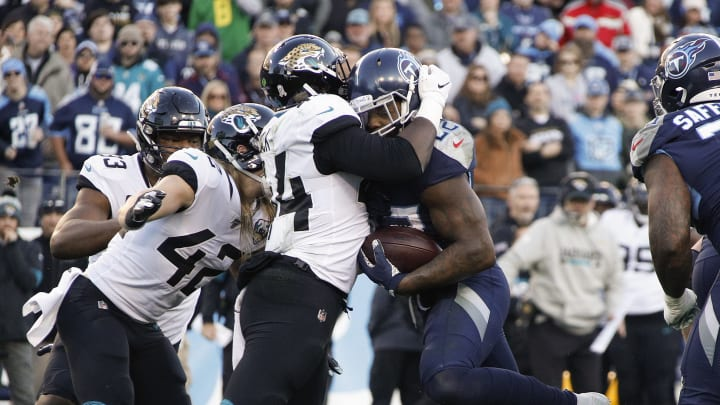 NASHVILLE, TENNESSEE - NOVEMBER 24: Dawuane Smoot #94 of the Jacksonville Jaguars stands up running back Derrick Henry #22 of the Tennessee Titans on a short yardage play during the first half at Nissan Stadium on November 24, 2019 in Nashville, Tennessee. (Photo by Frederick Breedon/Getty Images)