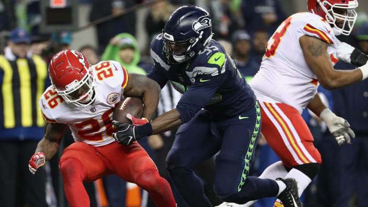 SEATTLE, WA - DECEMBER 23:  Damien Williams #26 of the Kansas City Chiefs fumbles the ball in front of Dion Jordan #95 of the Seattle Seahawks during the second quarter of the game at CenturyLink Field on December 23, 2018 in Seattle, Washington.  (Photo by Abbie Parr/Getty Images)