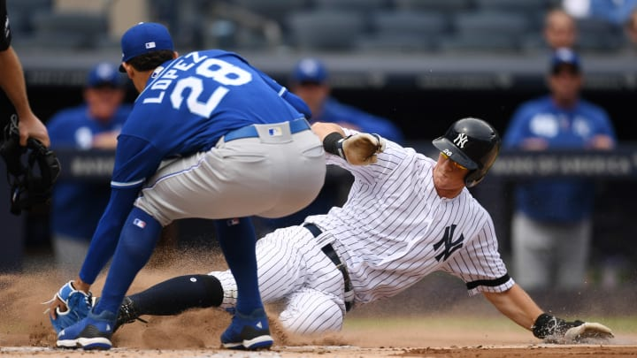 NEW YORK, NEW YORK - APRIL 21: DJ LeMahieu #26 of the New York Yankees slides into home as Jorge Lopez #28 of the Kansas City Royals attempts to get the out during the first inning of the game at Yankee Stadium on April 21, 2019 in the Bronx borough of New York City. (Photo by Sarah Stier/Getty Images)