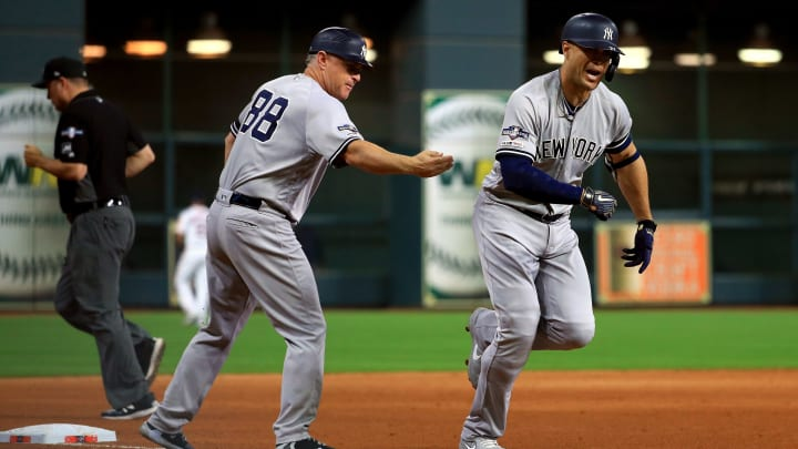 HOUSTON, TEXAS - OCTOBER 12:  Giancarlo Stanton #27 of the New York Yankees is congratulated by his third base coach Phil Nevin #88 after his solo home run against the Houston Astros during the sixth inning in game one of the American League Championship Series at Minute Maid Park on October 12, 2019 in Houston, Texas. (Photo by Mike Ehrmann/Getty Images)
