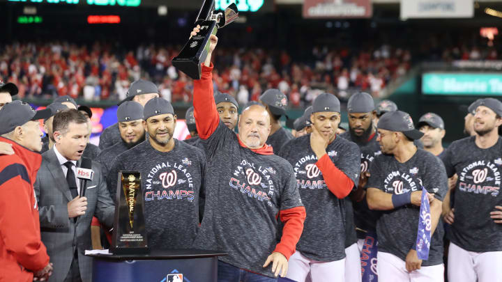 WASHINGTON, DC - OCTOBER 15: General manager Mike Rizzo and Manager Dave Martinez #4 of the Washington Nationals celebrate with the trophy after winning game four and the National League Championship Series against the St. Louis Cardinals at Nationals Park on October 15, 2019 in Washington, DC. (Photo by Rob Carr/Getty Images)