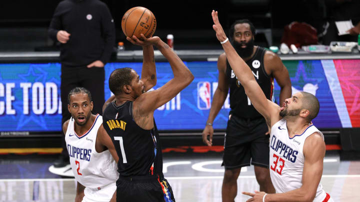 Kevin Durant goes up as James Harden watches