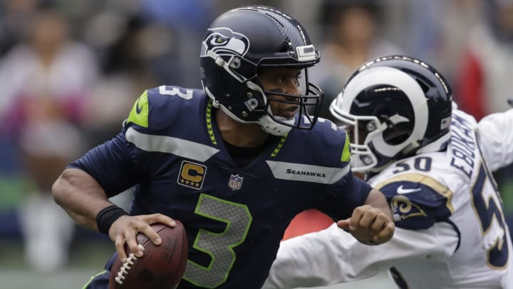 SEATTLE, WA - OCTOBER 07: Quarterback Russell Wilson #3 of the Seattle Seahawks rolls out of the pocket to avoid linebacker Samson Ebukam #50 of the Los Angeles Rams during a game at CenturyLink Field on October 7, 2018 in Seattle, Washington. The Rams won the game 33-31. (Photo by Stephen Brashear/Getty Images)