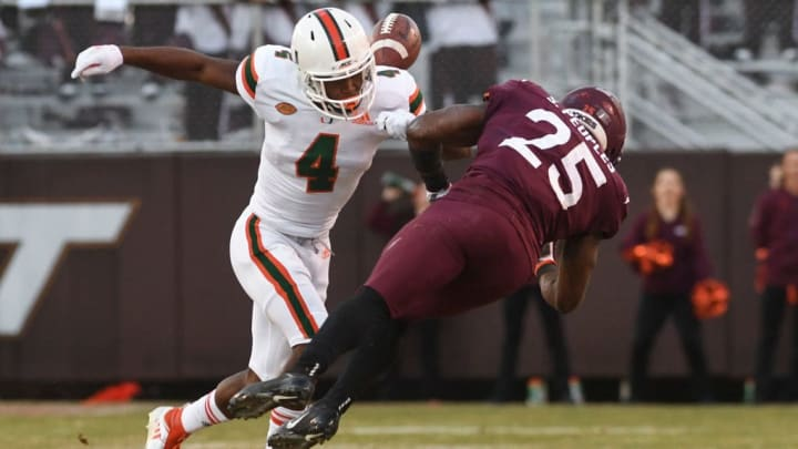 BLACKSBURG, VA - NOVEMBER 17: Defensive back Jaquan Johnson #4 of the Miami Hurricanes knocks the ball free form running back Steven Peoples #25 of the Virginia Tech Hokies in the first half at Lane Stadium on November 17, 2018 in Blacksburg, Virginia. Each week a different player wears #25 to honor former head coach Frank Beamer. (Photo by Michael Shroyer/Getty Images)
