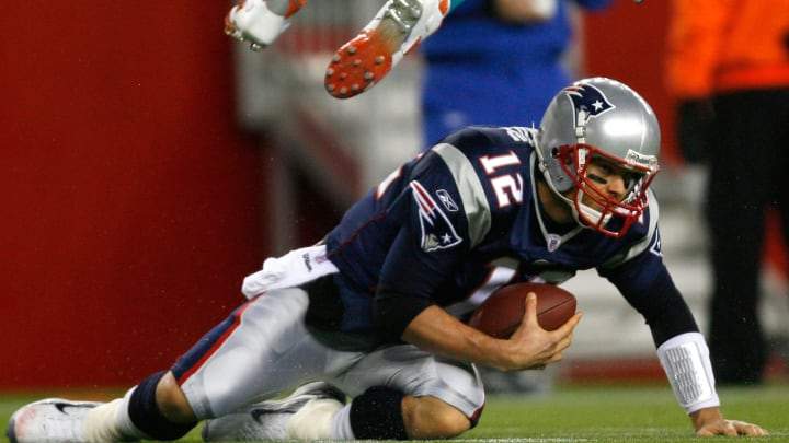 FOXBORO, MA - DECEMBER 23: Tom Brady #12 of the New England Patriots slides for a first down as Jason Taylor #99 of the Miami Dolphins jumps to avoid a collision at Gillette Stadium on December 23, 2007 in Foxboro, Massachusetts. Patriots won 28-7. (Photo by Jim Rogash/Getty Images)