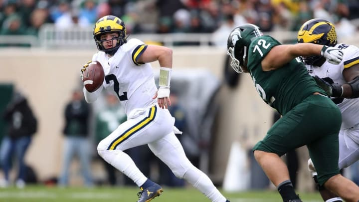 EAST LANSING, MI - OCTOBER 20:  Shea Patterson #2 of the Michigan Wolverines looks for a open receiver while being chased by Mike Panasiuk #72 of the Michigan State Spartans during the second quarter at Spartan Stadium on October 20, 2018 in East Lansing, Michigan. (Photo by Gregory Shamus/Getty Images)