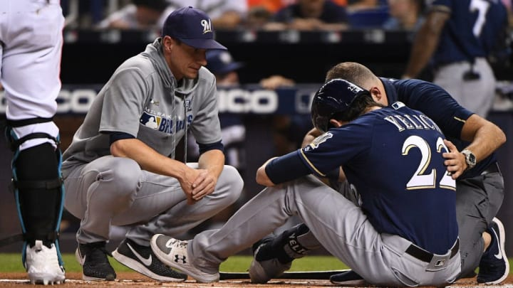 MIAMI, FLORIDA - SEPTEMBER 10: Craig Counsell #30 of the Milwaukee Brewers looks on as the medical staff tends to the injury of Christian Yelich #22 of the Milwaukee Brewers in the first inning against the Miami Marlins at Marlins Park on September 10, 2019 in Miami, Florida. Christian Yelich will miss the rest of the season after fracturing his right kneecap in Tuesday's victory over the Miami Marlins. (Photo by Mark Brown/Getty Images)