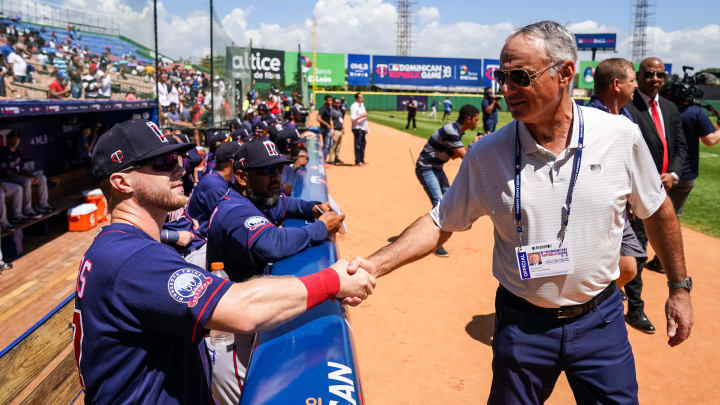 Rob Manfred and a baseball player.