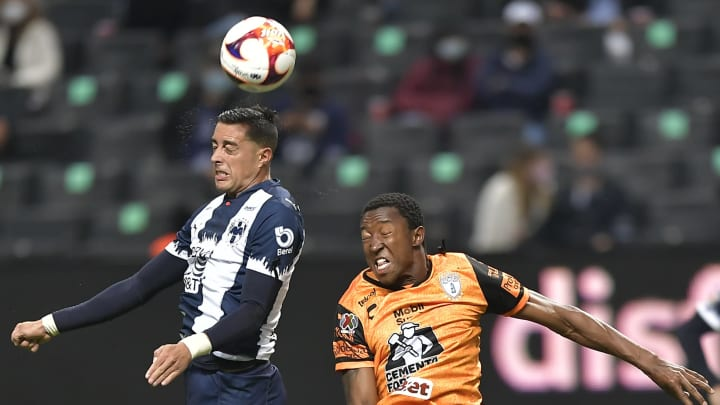 Jugadores de Pachuca y de Rayados de Monterrey pelean un balón.