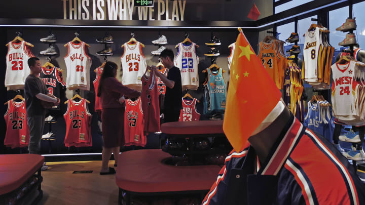 **IMAGE TAKEN WITH MOBILE PHONE CAMERA ** BEIJING, CHINA - OCTOBER 09: A Chinese flag is seen placed on a mannequin wearing the USA basketball uniform  as Chinese shoppers look at clothing in the NBA flagship retail store on October 9, 2019 in Beijing, China. The NBA is trying to salvage its brand in China amid criticism of its handling of a controversial tweet that infuriated the government and has jeopardized the leagues Chinese expansion. The crisis, triggered by a Houston Rockets executives tweet that praised protests in Hong Kong, prompted the Chinese Basketball Association to suspend its partnership with the league. The backlash continued with state-owned television CCTV scrapping its plans to broadcast pre-season games in Shanghai and Shenzhen, and the cancellation of other promotional fan events.  The league issued an apology, though NBA Commissioner Adam Silver angered Chinese officials further when he defended the right of players and team executives to free speech. China represents a lucrative market for the NBA, which stands to lose millions of dollars in revenue and threatens to alienate Chinese fans.  Many have taken to Chinas social media platforms to express their outrage and disappointment that the NBA would question the countrys sovereignty over Hong Kong which has been mired in anti-government protests since June.(Photo by Kevin Frayer/Getty Images)