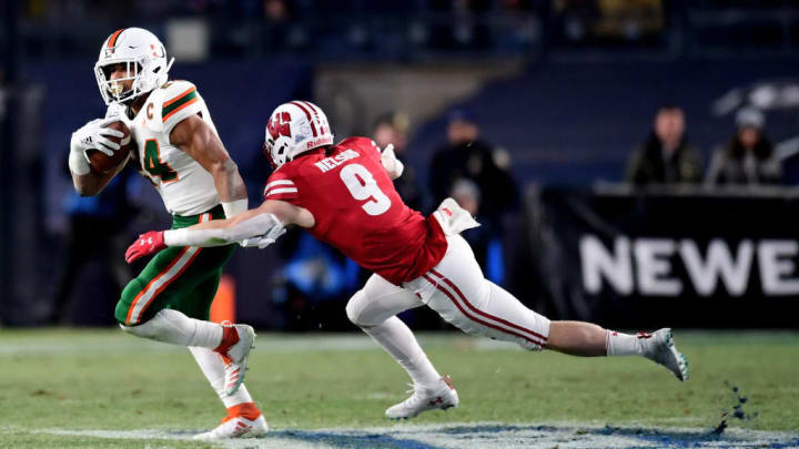 NEW YORK, NEW YORK - DECEMBER 27: Scott Nelson #9 of the Wisconsin Badgers tackles Travis Homer #24 of the Miami Hurricanes in the first quarter of the New Era Pinstripe Bowl at Yankee Stadium on December 27, 2018 in the Bronx borough of New York City. (Photo by Sarah Stier/Getty Images)