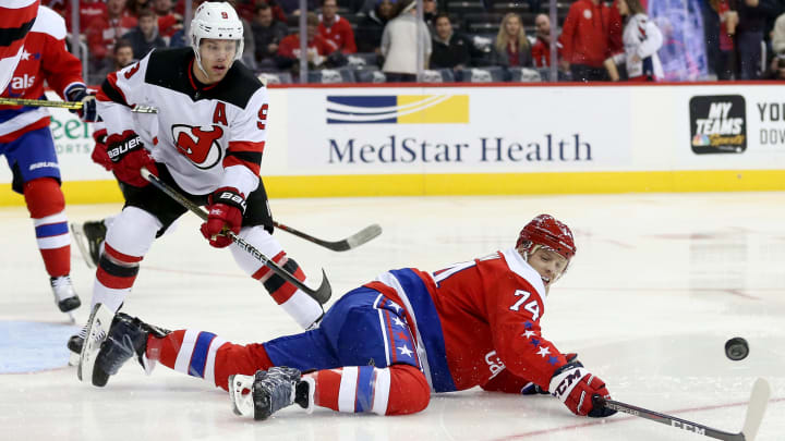 WASHINGTON, DC - NOVEMBER 30: John Carlson #74 of the Washington Capitals and Taylor Hall #9 of the New Jersey Devils go after the puck during the first period at Capital One Arena on November 30, 2018 in Washington, DC. (Photo by Will Newton/Getty Images)
