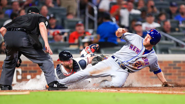 ATLANTA, GA - AUGUST 13: Todd Frazier #21 of the New York Mets is tagged out by Brian McCann #16 of the Atlanta Braves at home plate in front of umpire Dan Bellino #2 in the sixth inning at SunTrust Park on August 13, 2019 in Atlanta, Georgia. (Photo by Carmen Mandato/Getty Images)