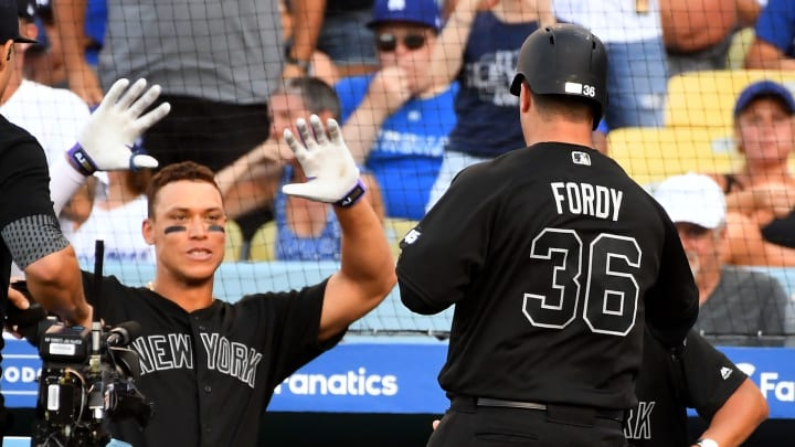 LOS ANGELES, CA - AUGUST 25: Mike Ford #36 is congratulated by Aaron Judge #99 of the New York Yankees after hittng a solo home run in the sixth inning of the game against the Los Angeles Dodgers at Dodger Stadium on August 25, 2019 in Los Angeles, California. Teams are wearing special color schemed uniforms with players choosing nicknames to display for Players' Weekend. (Photo by Jayne Kamin-Oncea/Getty Images)
