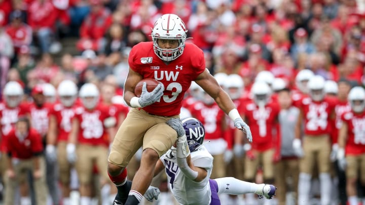 MADISON, WISCONSIN - SEPTEMBER 28:  Jonathan Taylor #23 of the Wisconsin Badgers runs with the ball while being tackled by Travis Whillock #7 of the Northwestern Wildcats in the first quarter at Camp Randall Stadium on September 28, 2019 in Madison, Wisconsin. (Photo by Dylan Buell/Getty Images)