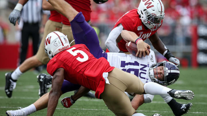 MADISON, WISCONSIN - SEPTEMBER 28:  Hunter Johnson #15 of the Northwestern Wildcats runs with the ball while being tackled by Rachad Wildgoose #5 of the Wisconsin Badgers in the second quarter at Camp Randall Stadium on September 28, 2019 in Madison, Wisconsin. (Photo by Dylan Buell/Getty Images)