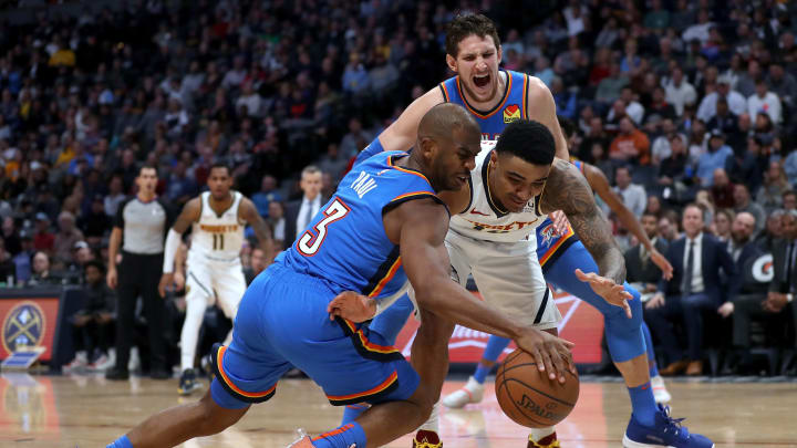 Chris Paul of the Thunder and Gary Harris of the Nuggets diving for a loose ball
