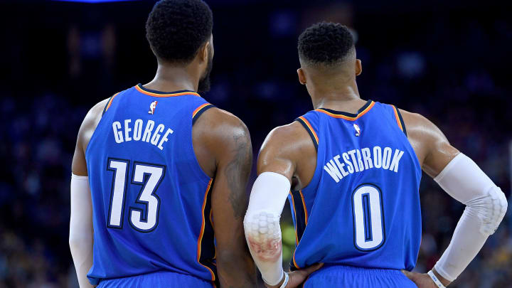 OAKLAND, CA - FEBRUARY 06:  Paul George #13 and Russell Westbrook #0 of the Oklahoma City Thunder looks on against the Golden State Warriors during the second half of their NBA basketball game at ORACLE Arena on February 6, 2018 in Oakland, California. NOTE TO USER: User expressly acknowledges and agrees that, by downloading and or using this photograph, User is consenting to the terms and conditions of the Getty Images License Agreement.  (Photo by Thearon W. Henderson/Getty Images)