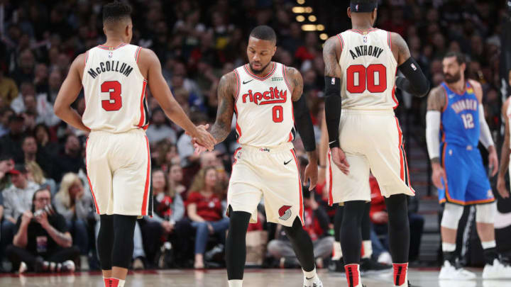 PORTLAND, OREGON - NOVEMBER 27: CJ McCollum #3 and Damian Lillard #0 high five alongside Carmelo Anthony #00 of the Portland Trail Blazers in the first quarter against the Oklahoma City Thunder during their game at Moda Center on November 27, 2019 in Portland, Oregon. NOTE TO USER: User expressly acknowledges and agrees that, by downloading and or using this photograph, User is consenting to the terms and conditions of the Getty Images License Agreement (Photo by Abbie Parr/Getty Images)
