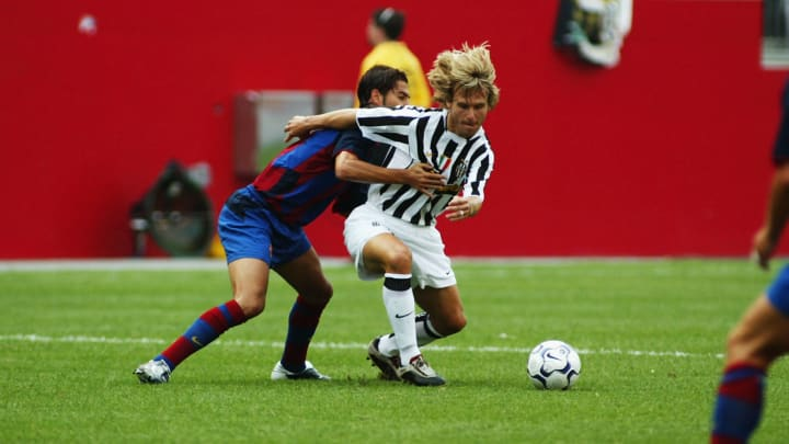 Pavel Nedved of Juventus holds off Gerard Lopez of Barcelona