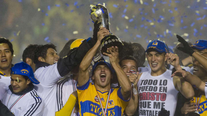 Players of Tigres hold their trophy duri