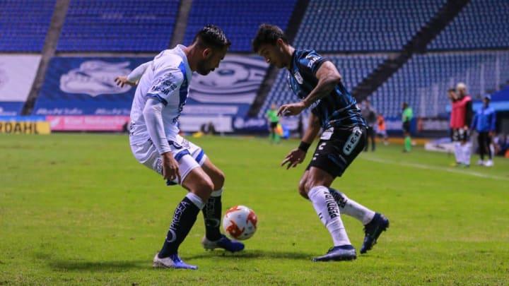 Jugadores de Puebla y Queretaro pelean un balón.