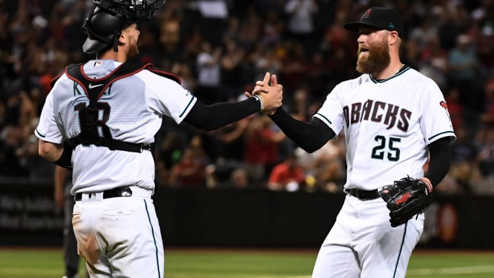 PHOENIX, ARIZONA - SEPTEMBER 27: Archie Bradley #25 and Carson Kelly #18 of the Arizona Diamondbacks celebrate a 6-3 win against the San Diego Padres at Chase Field on September 27, 2019 in Phoenix, Arizona. (Photo by Norm Hall/Getty Images)