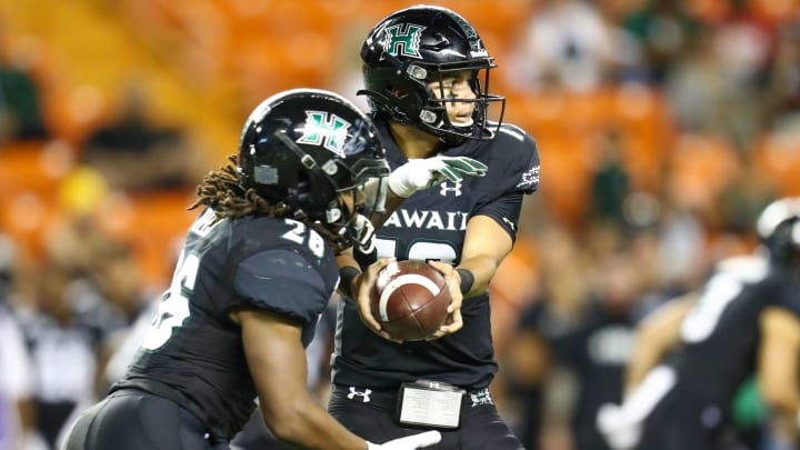 HONOLULU, HI - NOVEMBER 09: Chevan Cordeiro #12 of the Hawaii Rainbow Warriors hands the ball off to Miles Reed #26 of the Hawaii Rainbow Warriors during the second quarter of the game against the San Jose State Spartans at Aloha Stadium on November 9, 2019 in Honolulu, Hawaii. (Photo by Darryl Oumi/Getty Images)