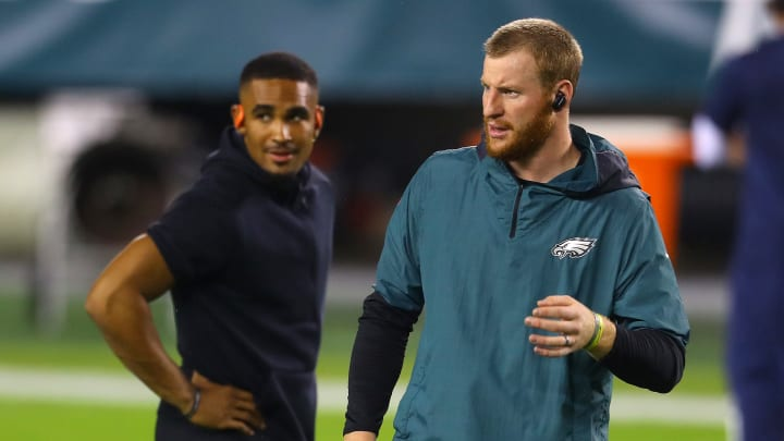Jalen Hurts looking over Carson Wentz's shoulder.