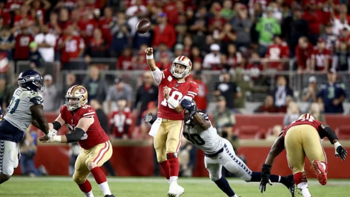 SANTA CLARA, CALIFORNIA - NOVEMBER 11: Quarterback Jimmy Garoppolo #10 of the San Francisco 49ers delivers a pass over the defense of the Seattle Seahawks in the game at Levi's Stadium on November 11, 2019 in Santa Clara, California. (Photo by Ezra Shaw/Getty Images)