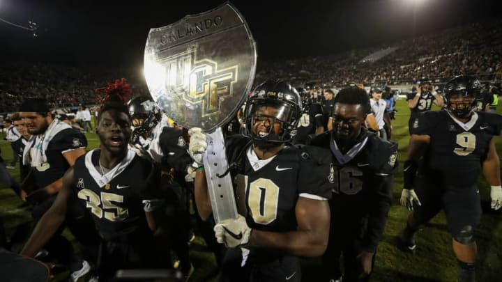 ORLANDO, FL - NOVEMBER 24: Titus Davis #10 of the UCF Knights holds the War on I-4 trophy after a game against the South Florida Bulls at Spectrum Stadium on November 24, 2017 in Orlando, Florida. UCF Knights defeated South Florida Bulls 49-42. (Photo by Logan Bowles/Getty Images)