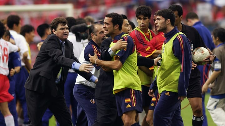 Spain coach Jose Antonio Camacho restrains his players from arguing with referee Gamal Ghandour