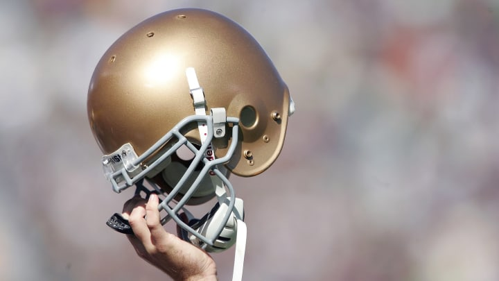A Notre Dame helmet held in the air symbolically.