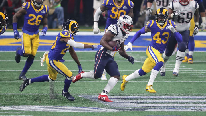 ATLANTA, GA - FEBRUARY 03: Sony Michel #26 of the New England Patriots runs the ball against Lamarcus Joyner #20 and John Johnson III #43 of the Los Angeles Rams in the second half during Super Bowl LIII at Mercedes-Benz Stadium on February 3, 2019 in Atlanta, Georgia.  (Photo by Elsa/Getty Images)