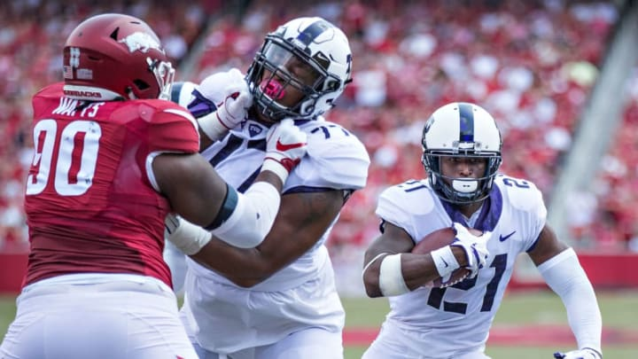 FAYETTEVILLE, AR - SEPTEMBER 9:  Kyle Hicks #21 runs the ball behind the blocking of Lucas Niang #77 of the TCU Horned Frogs during a game against the Arkansas Razorbacks at Donald W. Reynolds Razorback Stadium on September 9, 2017 in Fayetteville, Arkansas.  The Horn Frogs defeated the Razorbacks 28-7.  (Photo by Wesley Hitt/Getty Images)