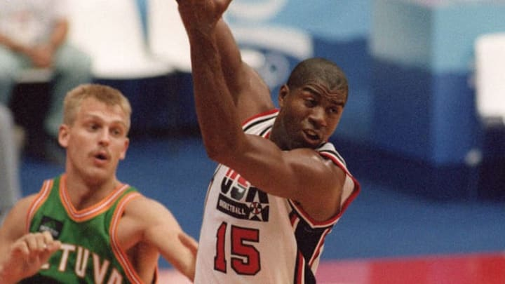 """BARCELONA, SPAIN - AUGUST 6:  US Earvin """"Magic"""" Johnson grabs a rebound in front of Lithuanian Gintaras Einikis, 06 August 1992, during their semi-final match at the 1992 Barcelona Olympic Games. The US """"Dream Team"""" beat Lithuania 127-76 and went on to play against Croatia in the final.  Magic won three MVP awards, made All-NBA first team from 1983-1991, played in twelve All-Star games, was named finals MVP on three separate occasions, won five NBA Championships in 1980, 1982, 1985, 1987, and 1988, and won the gold medal as part of the original """"Dream Team"""".  Magic Johnson, and Larry Bird, and Michael Jordan later, were responsible for basketball being the game that it is today.  (Photo credit should read DIMITRI MESSINIS/AFP/Getty Images)"""